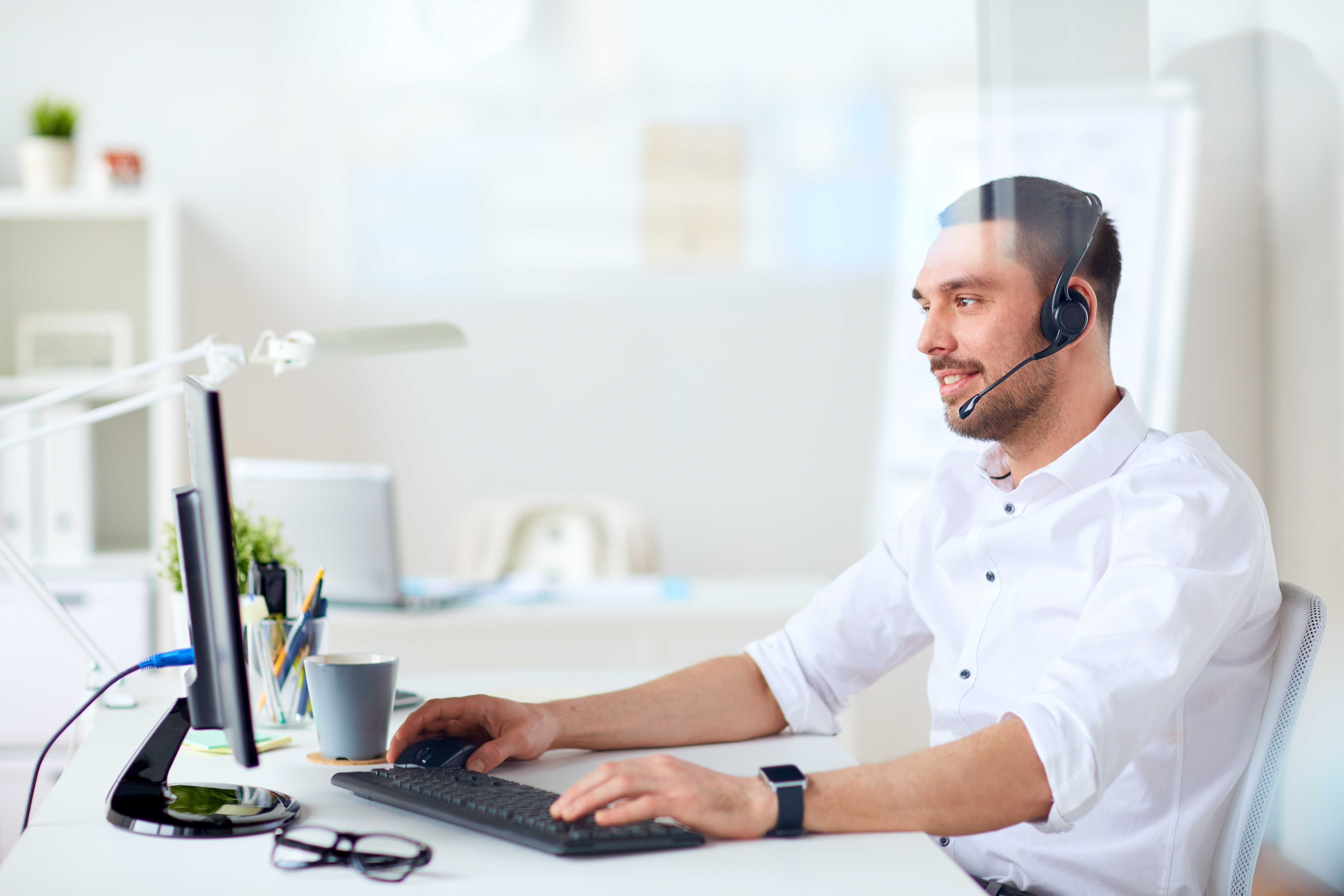 communication, business, people and technology concept - smiling businessman or helpline operator with headset and computer typing at office