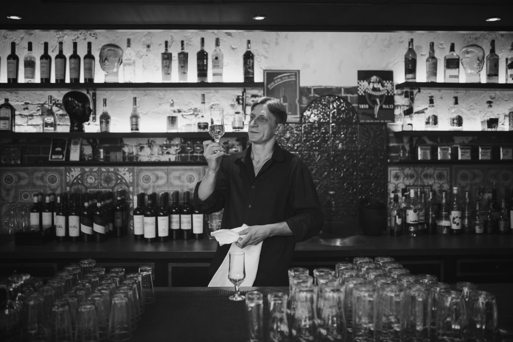 Barman at work in the pub rubs the glass. Black and white photo